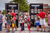 Photo of attendees looking at the Memorial Day Remembrance wall
