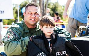 Child trying on police equipment at open house event
