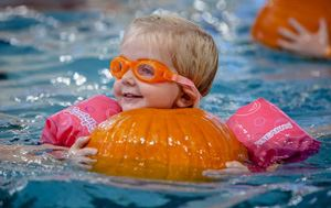 Young girl holding onto a pumpkin in the pool