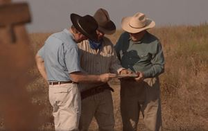 Three men looking a paper in a field