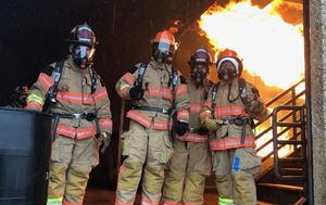 students from citizen&#39s fire academy standing in front of a controlled fire