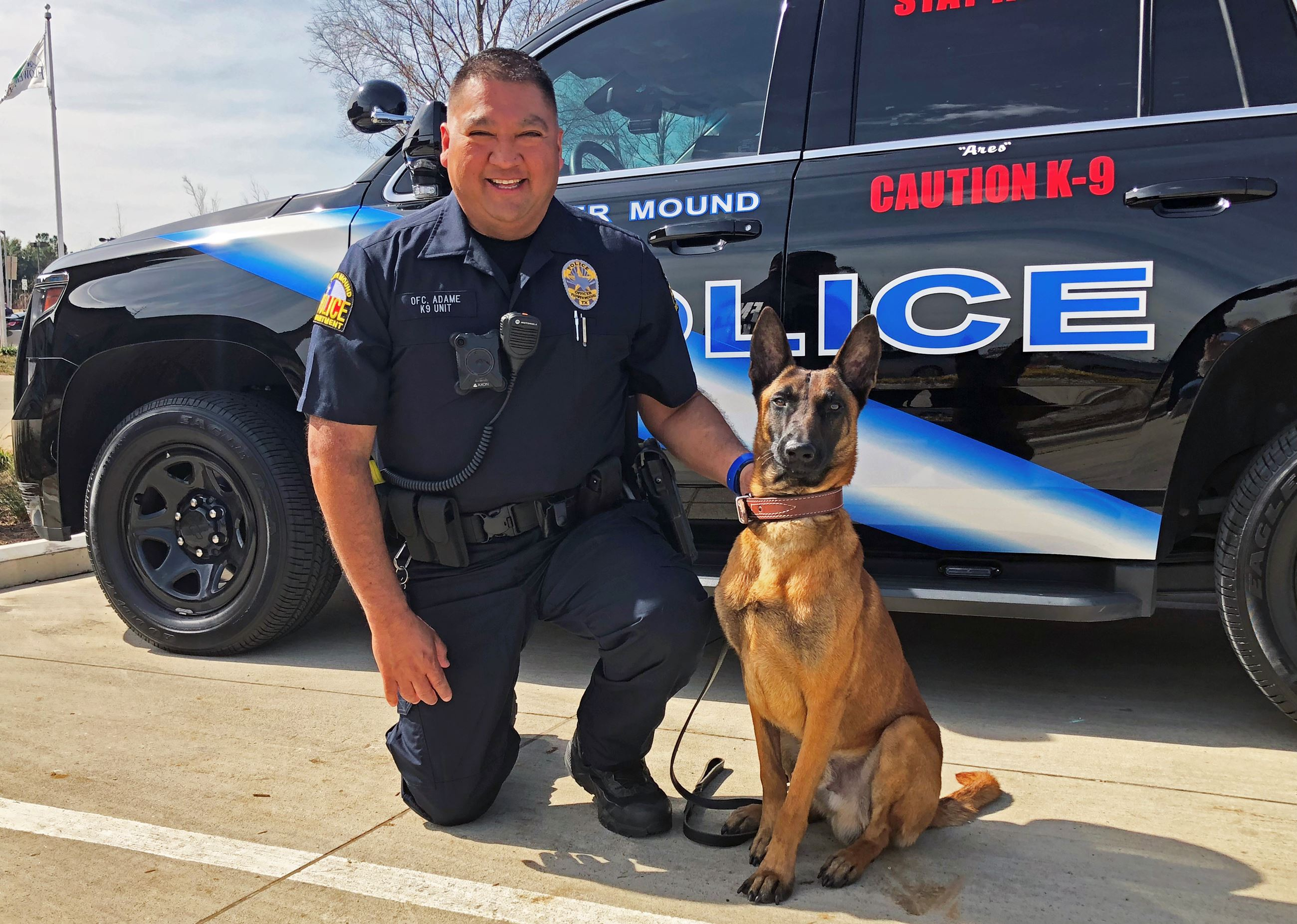 Flower Mound Police Officer kneeling  next to a dog officer
