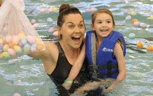 woman holding eggs in water with child in other arm during Underwater Egg Hunt