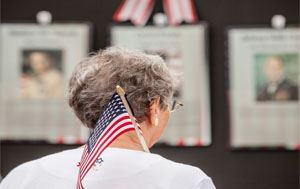 back of a lady's head holding a mini American Flag in front of Memorial Day Honor Wall