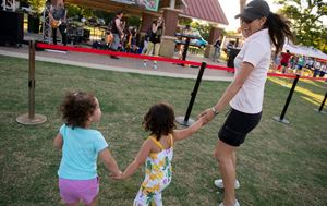 mom and two daughters dancing around outside with their hands in the air at Concerts in the Park