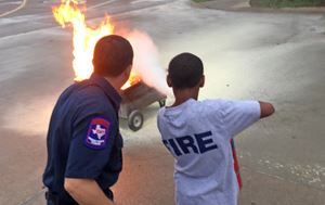 man and a boy facing away from the camera while the boy uses a fire hose to put out a fire during Fl
