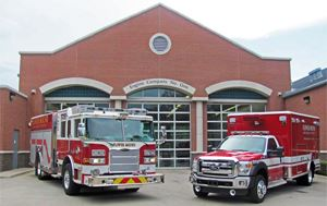 photo of the outside building of Flower Mound Fire Station No. 1 with a firetruck and medic car line