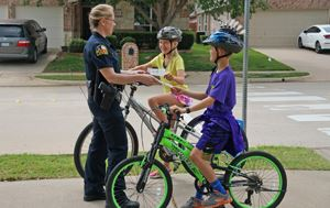 "Flower Mound police officer handing out ""Get the Scoop"" tickets to two children on bicycles we"