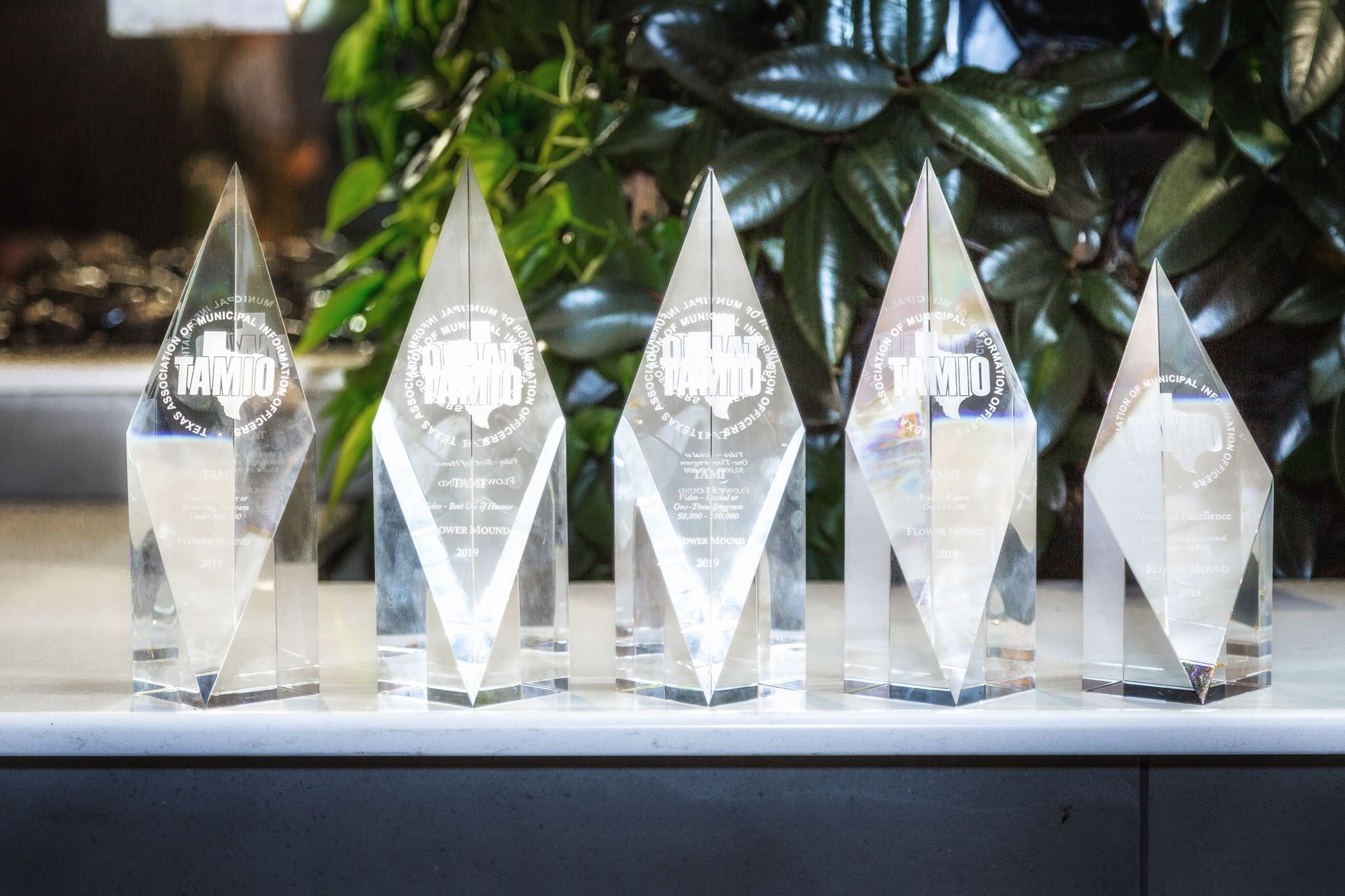 five crystal awards lined up in a row that the Flower Mound Communications Department received at th