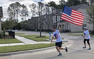 Person holding an American Flag and running during the Veterans Day Relay Run