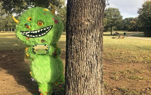 "green monster named the ""Flower Moundster"" peaking behind a tree at Heritage Park in Flower Mo"