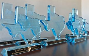 Texas shaped awards lined up in a row received from the Texas Association of Telecommunications Offi