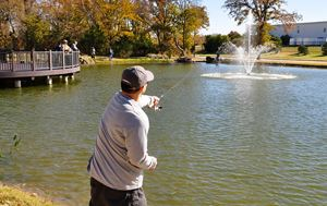 man throwing his fishing rod into the Heritage Park pond