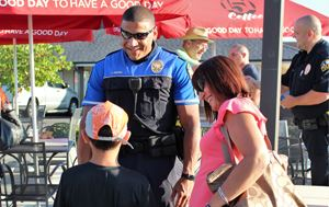 flower mound police officer smiling talking to a little boy and his mom outside of 151 coffee