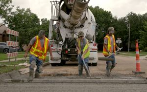 photo showing three Town Public Works employees fixing a street