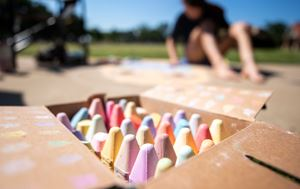 close up of pieces of chalk in a box with a girl drawing on the sidewalk in the background