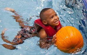 little boy swimming in the pool with a pumpkin