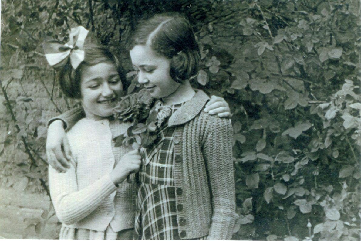 Two young girls from the 1940s smiling and looking at a flower