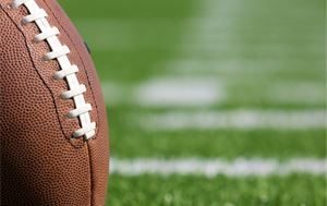 close up photo of a football with grass in background